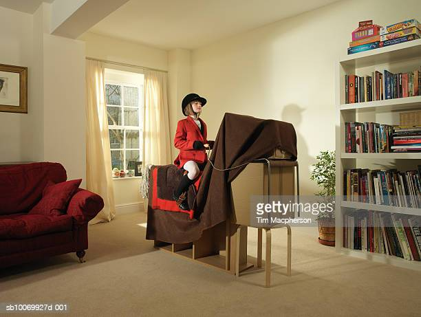 girl (8-9) pretending to ride horse made of furniture and blanket - aspirations stock pictures, royalty-free photos & images