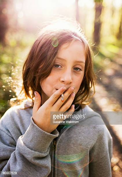 a girl pretending to smoke sweden. - little girl smoking cigarette stock photos and pictures