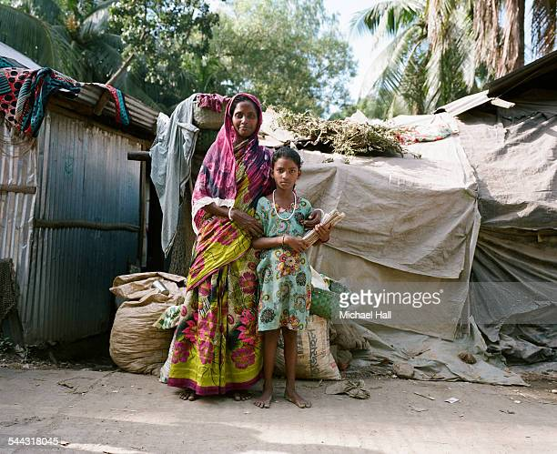 girl & proud mother from slum holding school books - bangladeshi school girls stock photos and pictures