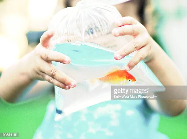 Girl proudly shows off a goldfish