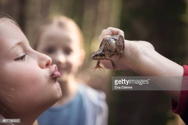 Girl puckering up to kiss a frog