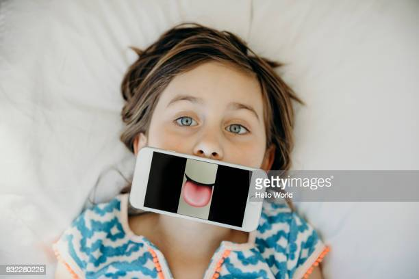 Girl pulling a funny face with smartphone over her mouth