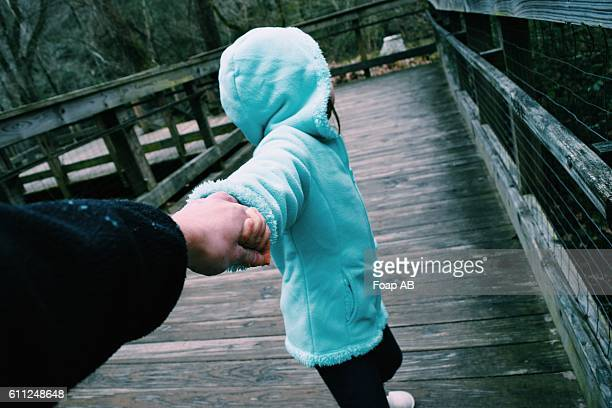 Girl pulling a person's hand on boardwalk