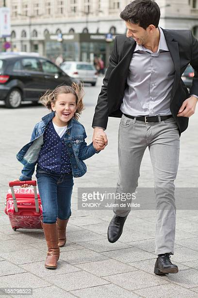 Girl pulling a trolley bag while running with her father