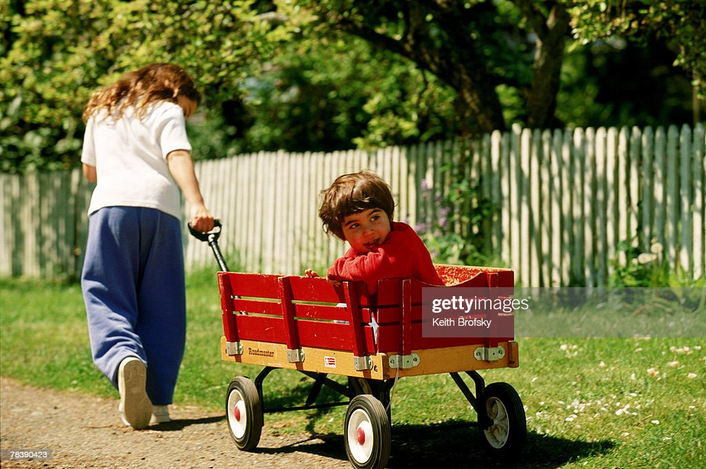 Boy Pulling Wagon : Girl pulling boy in wagon stock photo getty images