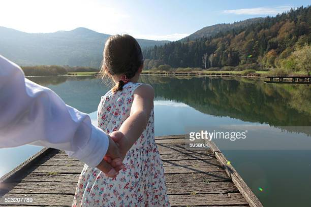 Girl pulling brother's hand to the nature