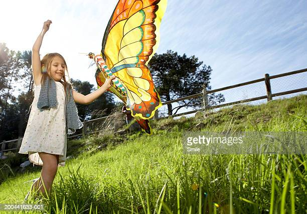 girl (8-10) pulling butterfly kite in field - kite toy stock photos and pictures