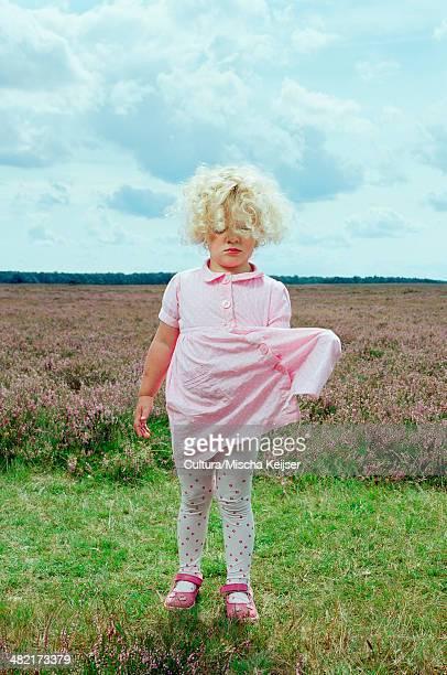 Girl pulling dress in field of flowers