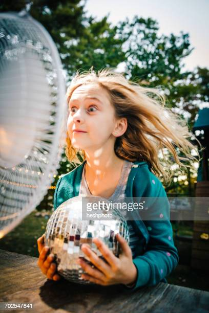 girl pulling face in front of windy electric fan at garden table - heshphoto stock pictures, royalty-free photos & images