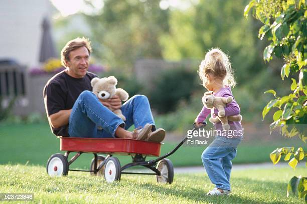 Girl Pulling Father on Wagon