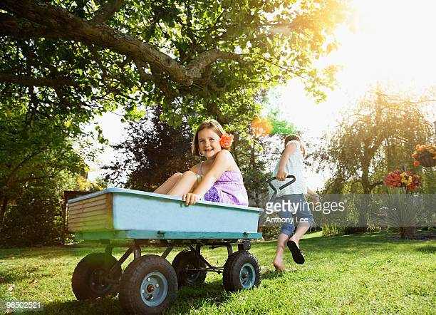 Girl pulling girl in wagon