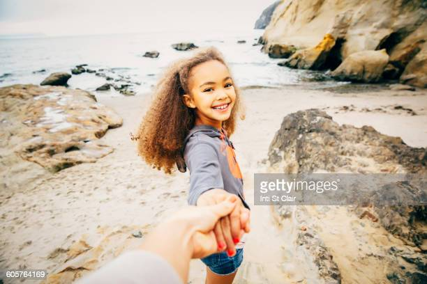 Girl pulling hand of mother on beach