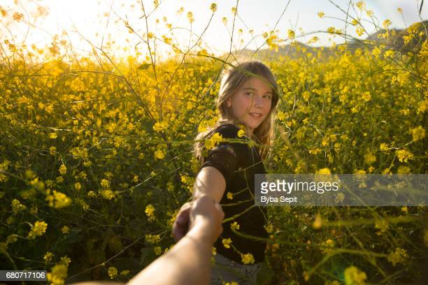 Girl pulling her mother into a yellow field of mustard wildflowers