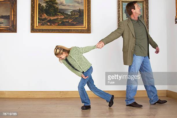 girl pulling man away from art - dragging stock pictures, royalty-free photos & images