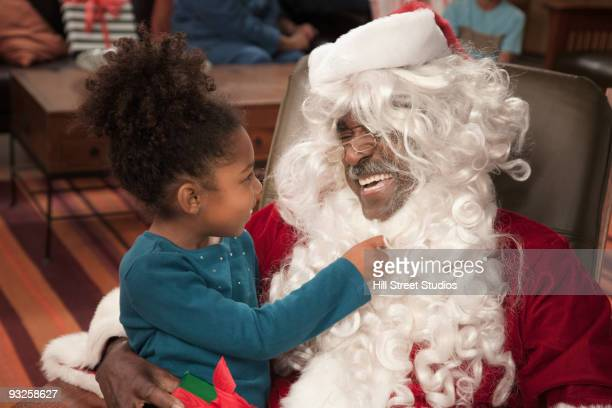 girl pulling on santa's beard - naughty santa stock photos and pictures