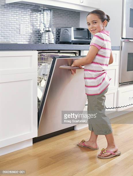 Girl (6-8) pulling open dishwasher door, smiling, portrait