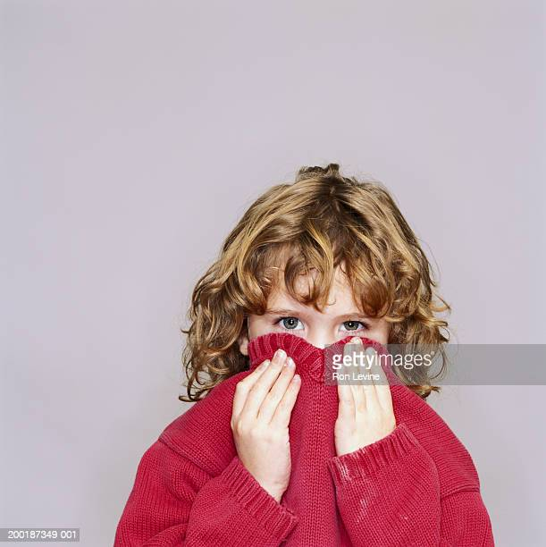 girl (5-7) pulling sweater collar over lower face, portrait - shy stock pictures, royalty-free photos & images