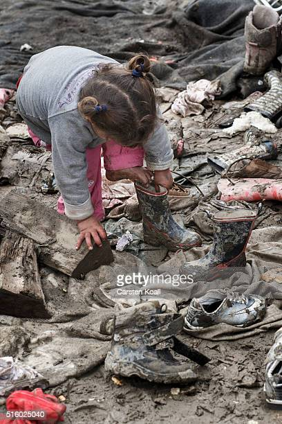 A girl pulls rubber boots between other muddy shoes at the Idomeni refugee camp on March 16 2016 in Idomeni Greece The decision by Macedonia to close...