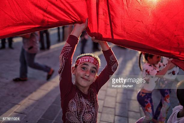 A girl pulls the edges of a giant Turkish flag located at Istanbul's central Taksim Square on July 19 2016 in Istanbul Turkey Clean up operations are...
