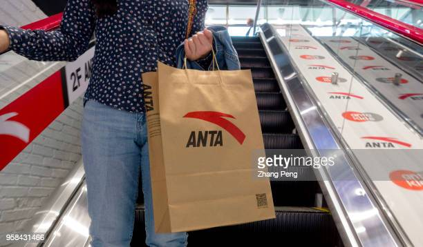 A girl purchased jogging shoes in an Anta store Anta sports China's leading sporting goods brand has a total revenue of 1669 billion Yuan in 2017...
