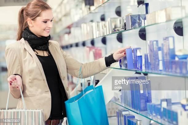 Chica de belleza y Cosméticos de compras en la tienda