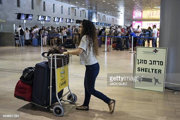 A girl pushes a trolley past a sign directing passengers to a shelter at Ben Gurion International airport near the Mediterranean Israeli coastal city...