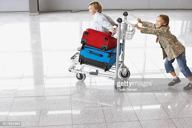 Girl pushing baggage cart in airport