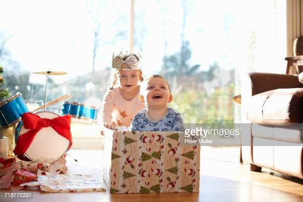 Girl pushing brother in cardboard box at christmas