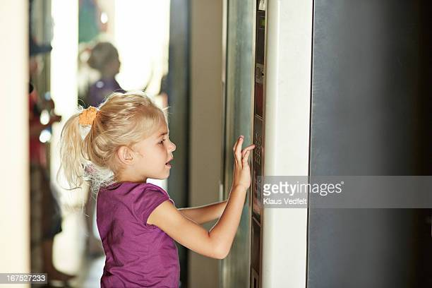 Girl pushing button on vending machine
