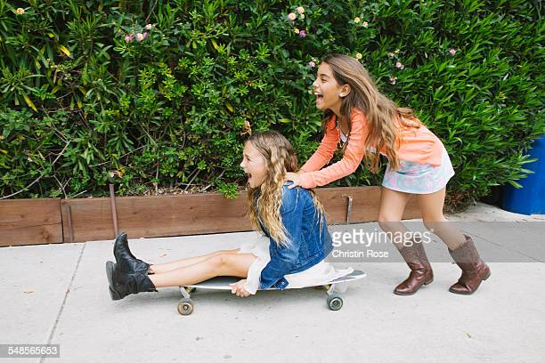 girl pushing friend on skateboard - only girls stock pictures, royalty-free photos & images