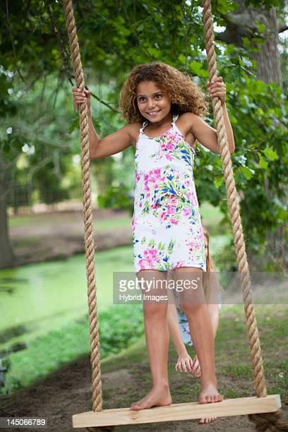 Girl pushing friend on tree swing