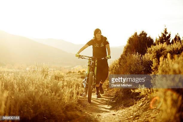 Girl pushing her mountain bike at sunset.