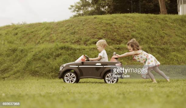 Girl pushing little brother in toy car