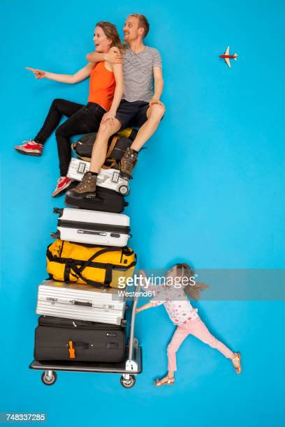 Girl pushing luggage trolley with parents sitting on top