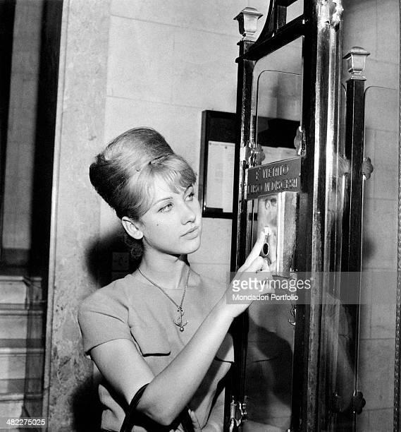 A girl pushing the lift button at publishing house Mondadori headquarters Milan October 1961