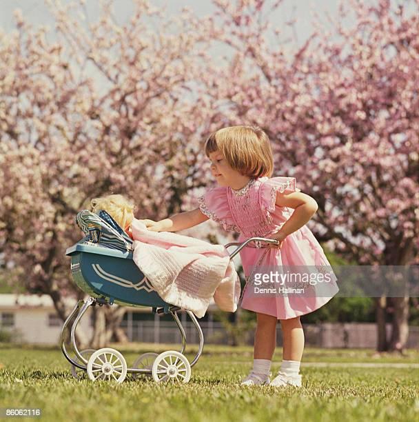 Girl pushing toy baby carriage