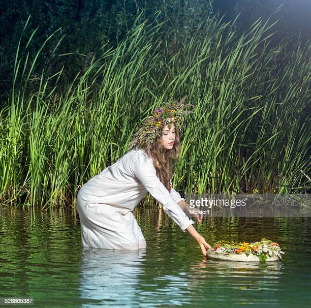 Girl puts wreath in river