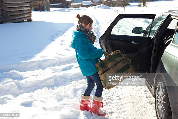 Girl putting a bag into a car in the snow