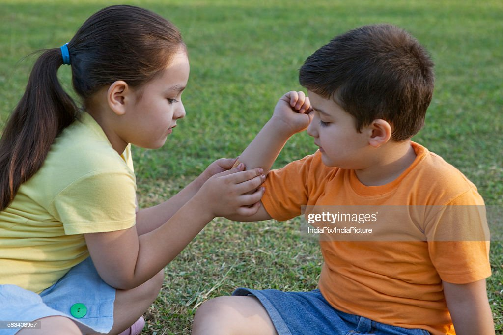 Girl putting band-aid on brothers arm : Stock Photo