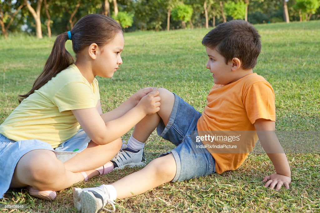 Girl putting band-aid on brothers leg : Stock Photo