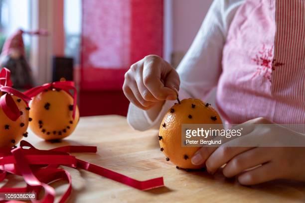girl putting cloves into an orange - cravo cravo da china imagens e fotografias de stock