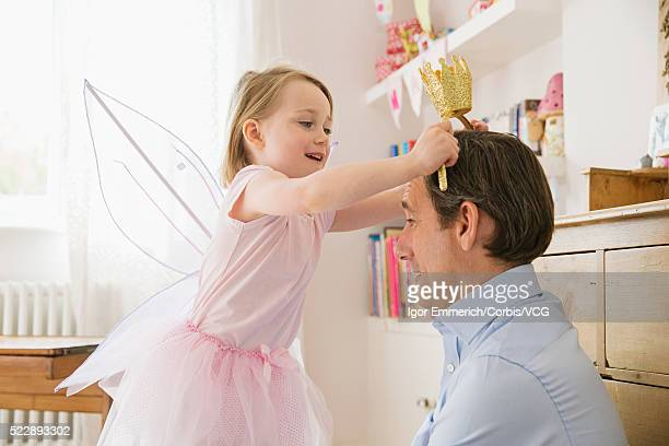 Girl (4-5) putting crown on father's head