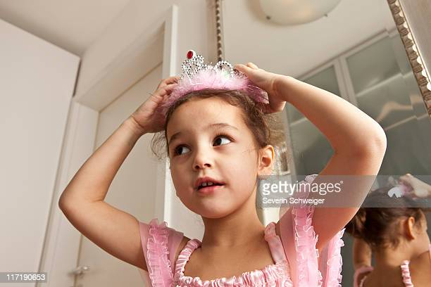 girl putting crown on her head - princess stock pictures, royalty-free photos & images