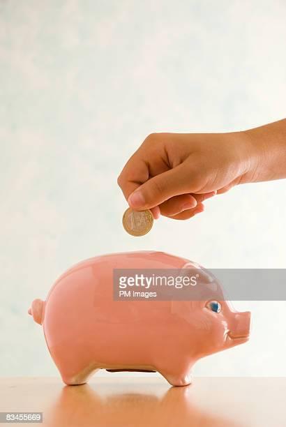 Girl putting Euro coin in piggy bank
