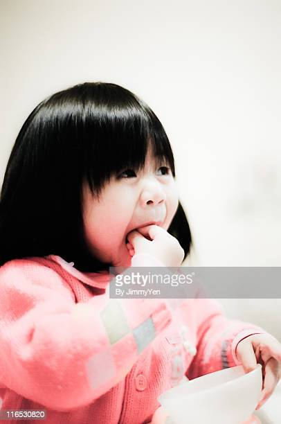 Girl putting hand in mouth