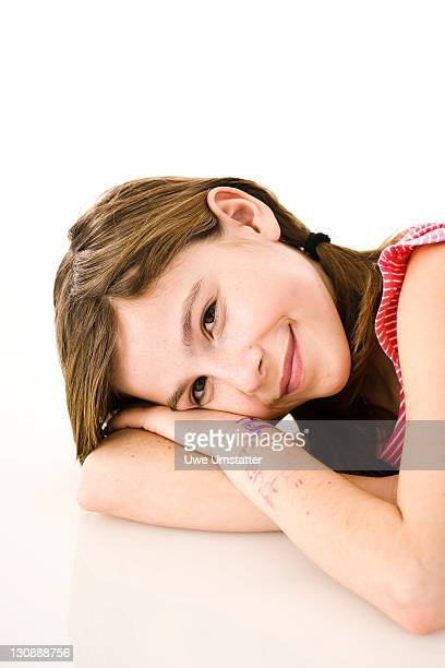 girl putting her head on folded arms - captions stock photos and pictures