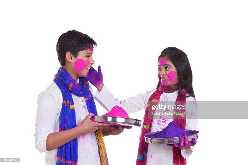 Girl putting holi colour on a boy : Stock Photo