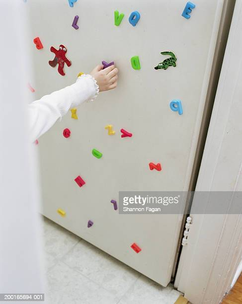 Girl putting magnet on refrigerator, close-up