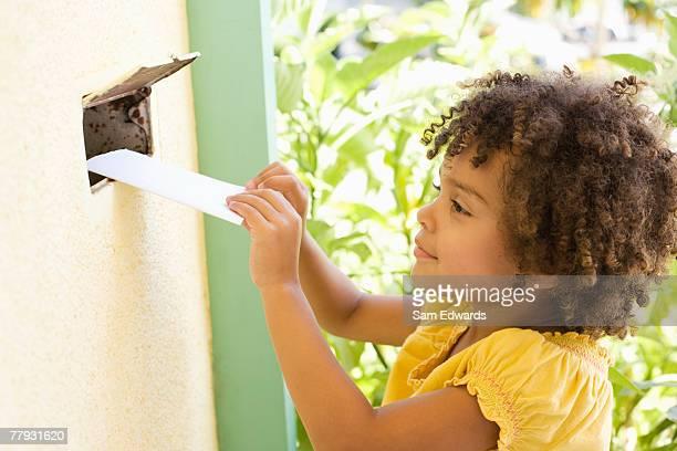 garota colocando correio através de uma caixa postal na porta - responder - fotografias e filmes do acervo