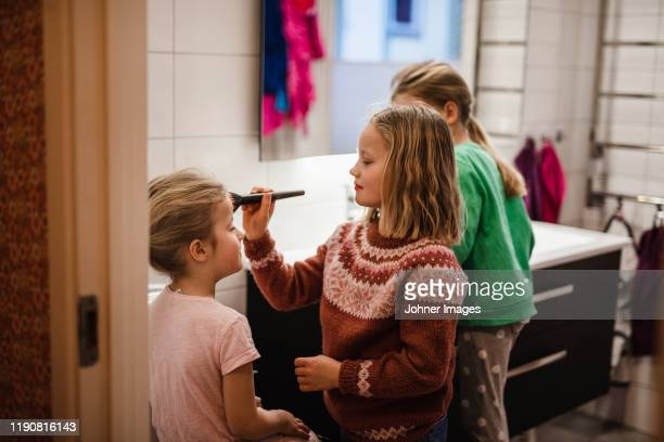 girl putting make-up on - sister stock pictures, royalty-free photos & images